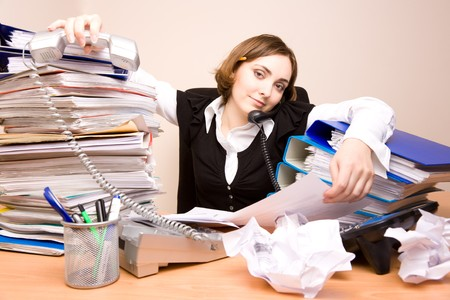appointee: Young secretary on the phone with tons of documents Stock Photo