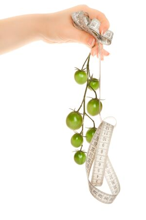 Womans hands holding a twig with green tomatoes and measuring tape photo