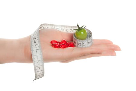 Womans hands holding green tomato, pills with measuring tape isolated on white photo