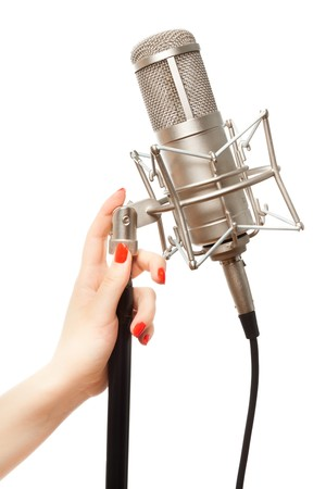 arms in air: Womans hand with red nails holding microphone stand Stock Photo