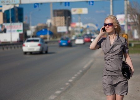call out: Woman in grey dress walking and calling by phone outdoors