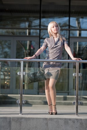 Beautiful blond woman standing near shopping center photo