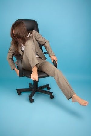 falling out: Woman in office chair trying not to fall
