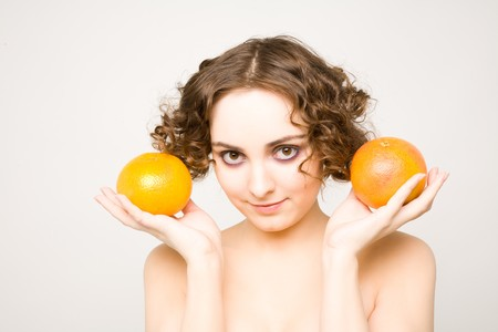 Beautiful curly girl holding grapefruits photo