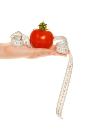 Womans hand holding tomatoes with tape measure isolated on white photo