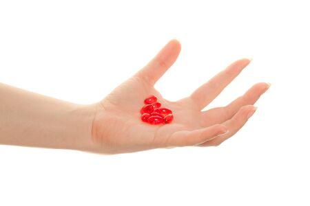 Womans hand holding   red pills isolated on white photo