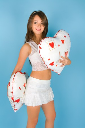 Beautiful young woman with two heart shaped pillows photo