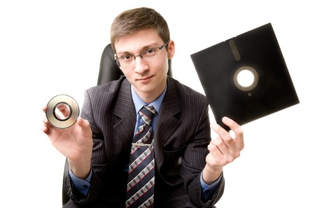 Young man with 8 inch floppy disk and CD photo