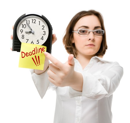 expires: Girl points to clock with deadline sign (focus on clock)