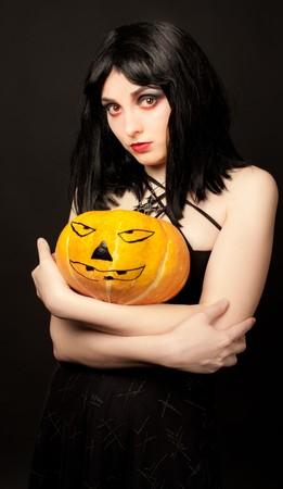Strange woman in black dress holding halloween pumpkin photo