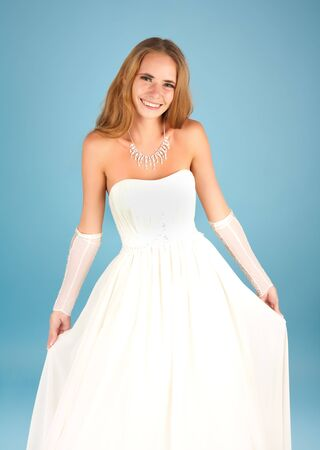 Beautiful bride in wedding dress smiling on the blue background Stock Photo - 8054640