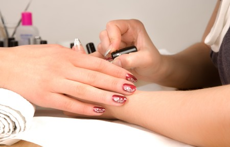 Womans hands nail brush drawing on nails photo