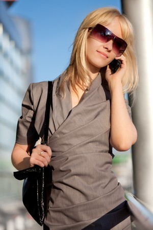 Beautiful woman in sunglasses with cellphone walking Stock Photo - 8054656