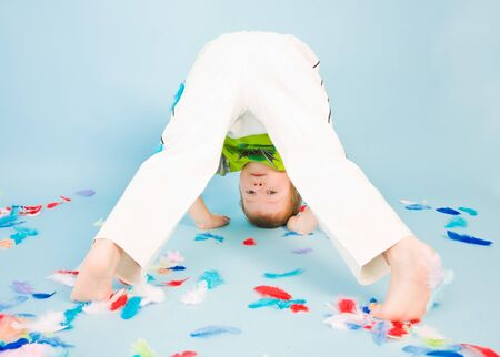 somersault: Boy playing with a lot of colorful feathers