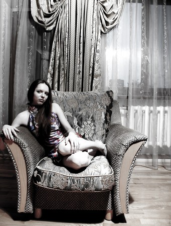 Sexy woman sitting on the armchair at home photo