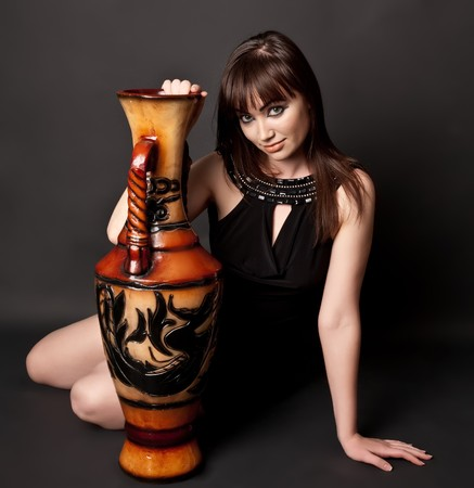Sexy woman with amphora sitting on the floor photo