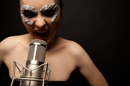 Young gothic singer standing with microphone and screaming photo