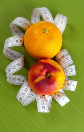 Concept of healthy food (orange, peach and tape measure) photo