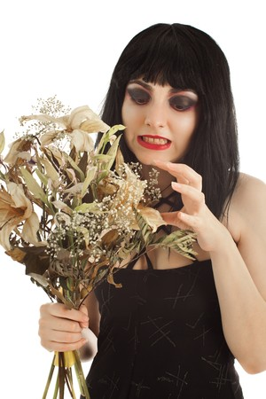 Witch with bunch of dry flowers looking crafty isolated on white photo
