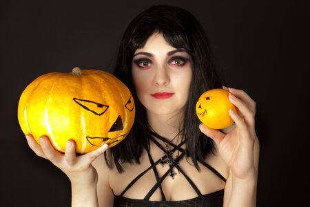 Woman with halloween makeup choosing between  a pumpkin or an orange photo