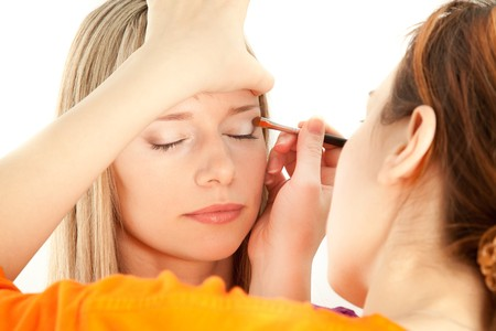 Woman applying makeup onto performers face photo