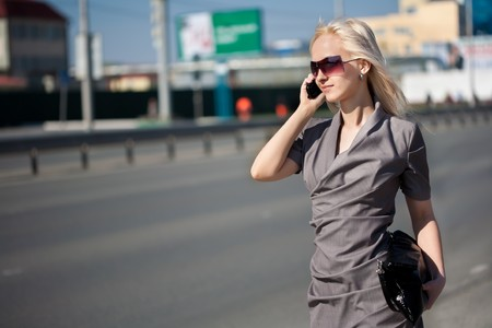 Woman in grey dress walking and calling by phone outdoors photo