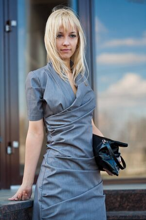 Young woman in grey dress and black clutch dreaming Stock Photo - 8054773