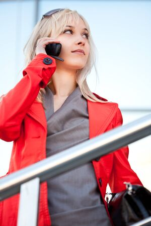 Beautiful woman in red jacket standing on the shop and calling to phone photo