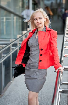 Beautiful woman in red jacket standing on the shop photo