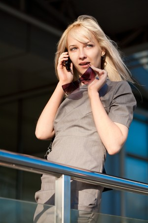 Woman calling by phone outdoors photo