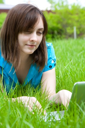 Smiling woman with laptop lying on the grass photo