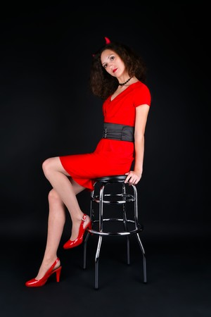 Beautiful woman in halloween costume sitting on the barchair photo