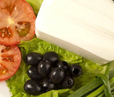 A plate of cut tomato, olives, lettuce and feta cheese photo