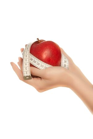 Womans hands holding red apple with measuring tape isolated photo