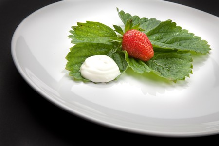 whig: A plate with strawberry and cream on the black background