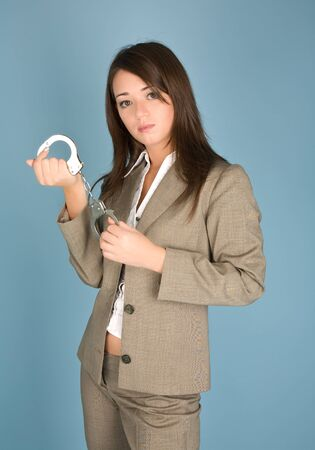 Woman holding a handcuffs standing on the blue background Stock Photo - 8159783