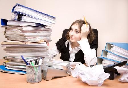 Junge geschäftsfrau mit Tonnen von Dokumenten denken