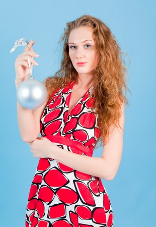 woman hanging toy: Beautiful woman in red dress smiling with silver new year ball on the blue background Stock Photo