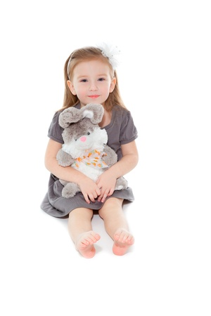 Little girl with toy sitting on the floor and smiling photo