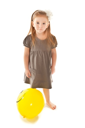 Little girl with yellow  toy balloon looking to the camera photo