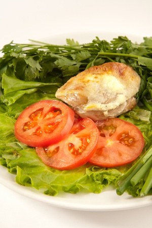 A plate with burning chicken, tomatoes, onion and lettuce photo