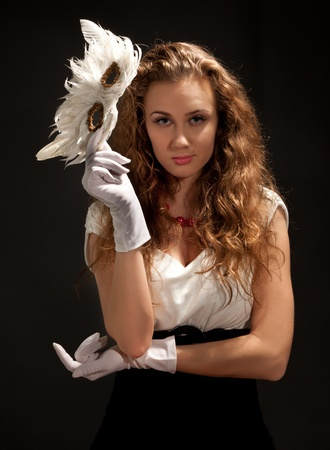 Beautiful woman in dress holding a mask and looking to the camera photo