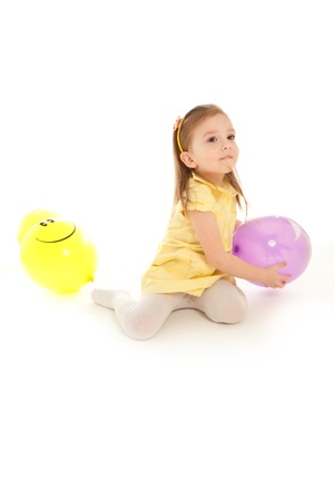 Funny little girl sitting on the floor and playing to balloon isolated photo