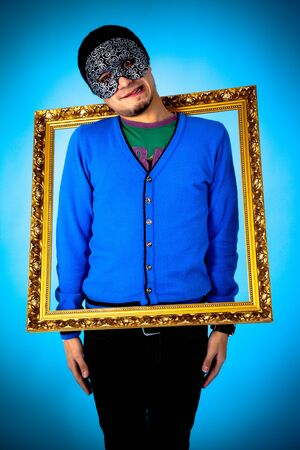 Young funny man with gold frame standing on the blue background photo