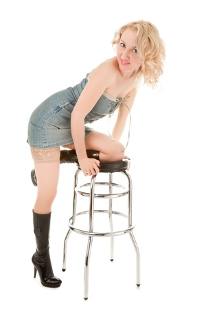 Sexy blond woman sitting on a bar chair isolated photo