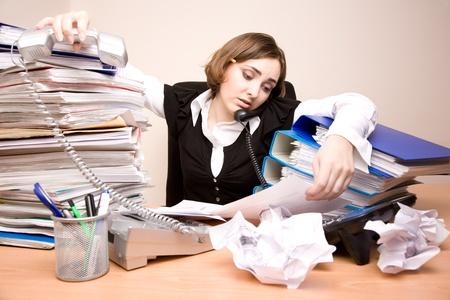 secretaria: Young cansado a Empresaria con toneladas de documentos llamada de tel�fono Foto de archivo