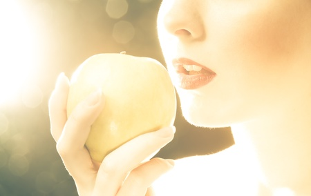 Bright picture of womans red lips with an apple photo