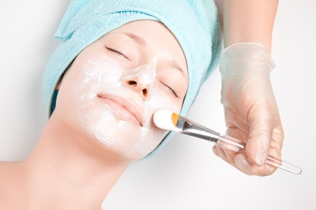 woman face cream: Young woman at spa procedures applying mask Stock Photo