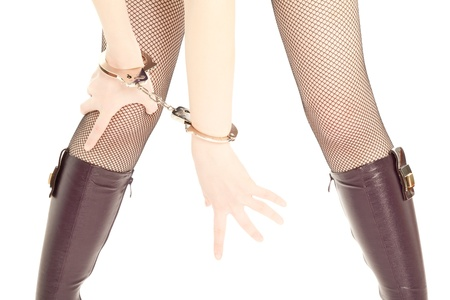 Woman's legs and hands with handcuffs isolated on white Stock Photo - 9317656