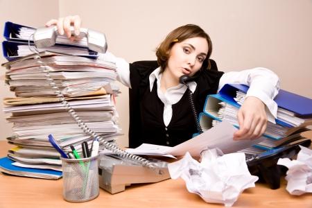 secretaries: Joven Secretario en el tel�fono con toneladas de documentos Foto de archivo